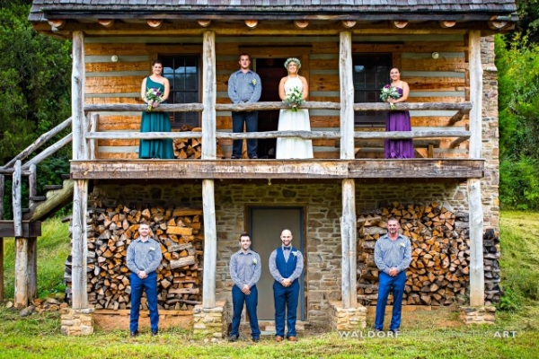 Bridal cabin with bridesmaids and groomsmen posing for photo at their barn wedding near Knoxville.