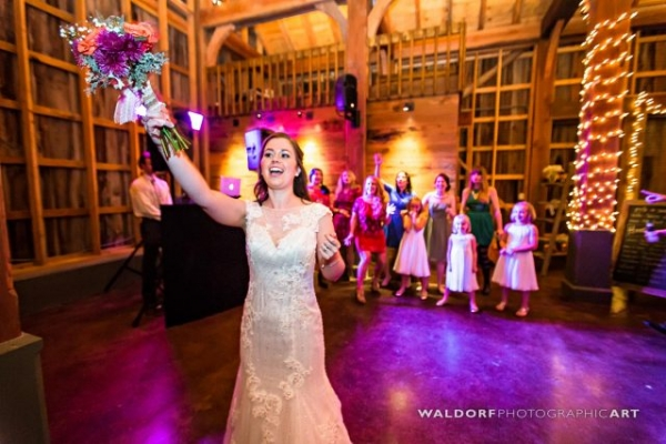 Throwing the bouquet in the barn from above at Pure Water Farm barn wedding near Gatlinburg.